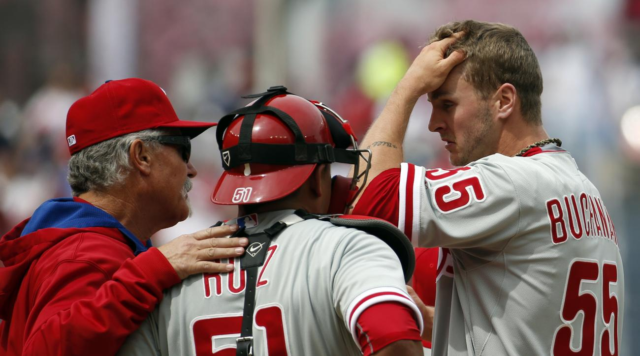 Philadelphia Phillies pitching coach Bob McClure, left, talks with catcher Carlos Ruiz (51) and starting pitcher David Buchanan (55) during the fifth inning of a baseball game against the Washington Nationals at Nationals Park, Sunday, April 19, 2015, in