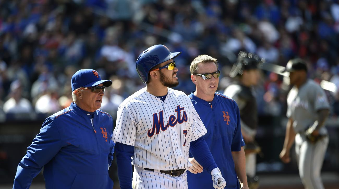 New York Mets manager Terry Collins, left, and a Mets trainer talk with catcher Travis d'Arnaud (7) after he was hit by a pitch thrown by Miami Marlins relief pitcher A.J. Ramos, right, in the seventh inning of a baseball game at Citi Field on Sunday, Apr