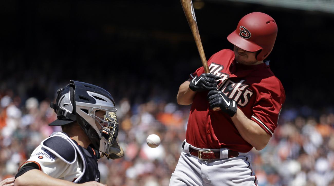 Arizona Diamondbacks' Jordan Pacheco, right, is hit by a pitch thrown by San Francisco Giants' Tim Hudson in the third inning of a baseball game Sunday, April 19, 2015, in San Francisco. Giants catcher Andrew Susac, left, looks on. (AP Photo/Ben Margot)