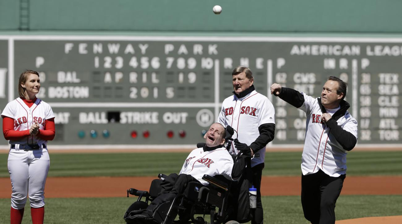 Dr. Bryan Lyons, right, throws out a ceremonial first pitch as father and son Boston Marathon race team Dick, second from right, and Rick Hoyt, center, look on before a baseball game between the Baltimore Orioles and the Boston Red Sox, Sunday, April 19,