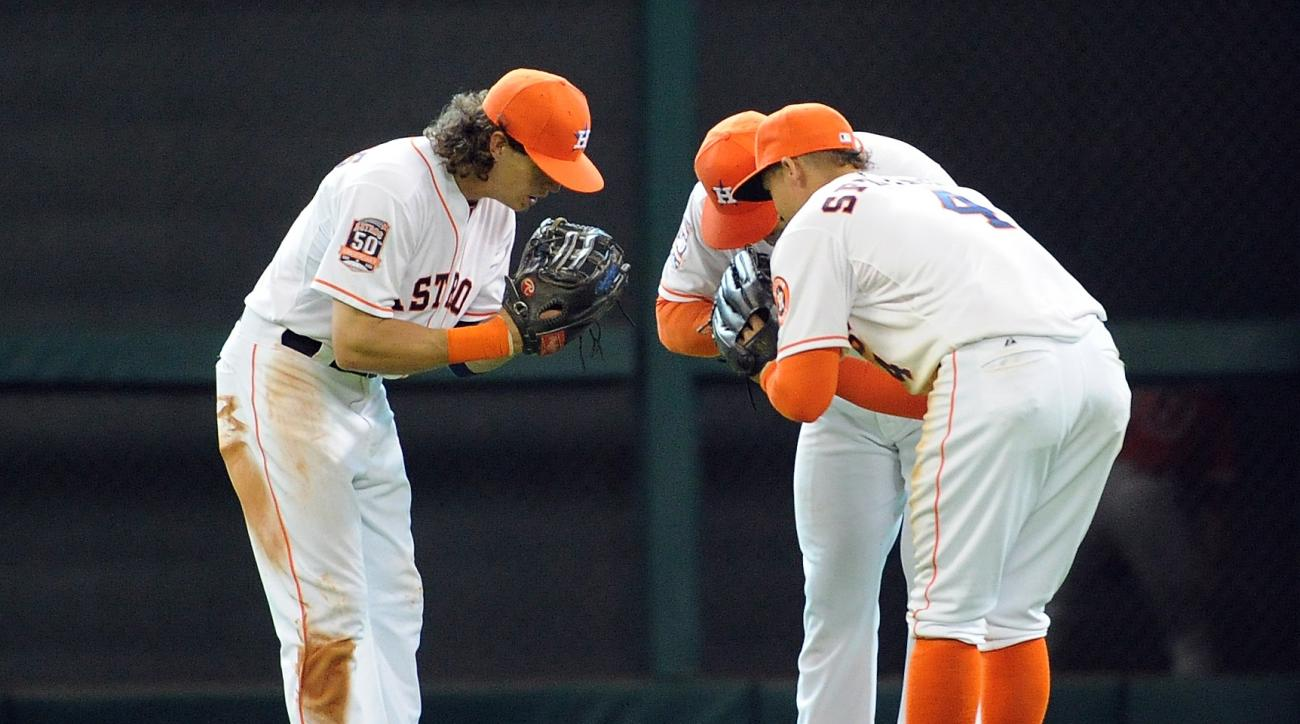 Houston Astros' outfielders Colby Rasmus, left, Jake Marisnick, center, and George Springer celebrate the Astros' 4-3 victory over the Los Angeles Angels in a baseball game, Sunday, April 19, 2015, at Minute Maid Park in Houston. (AP Photo/Eric Christian