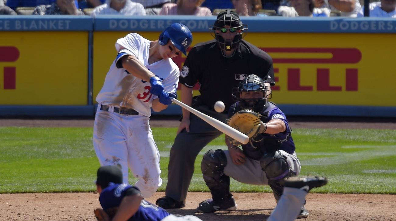 Los Angeles Dodgers' Joc Pederson, left, hits a solo home run as Colorado Rockies relief pitcher Scott Oberg, bottom watch along with catcher Michael McKenry, right, and home plate umpire Todd Tichenor during the fifth inning of a baseball game, Sunday, A