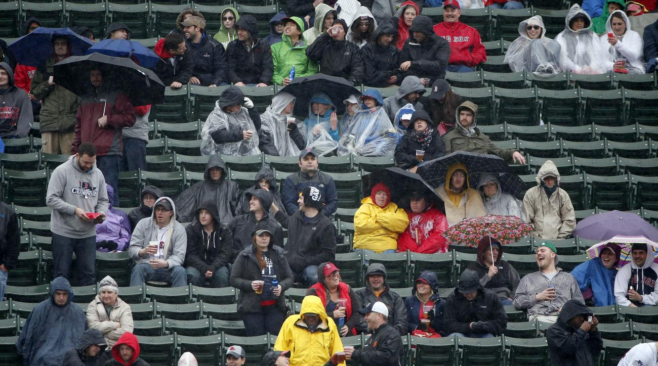 Fans sit in the rain during the fifth inning of a baseball game between the Boston Red Sox and the Baltimore Orioles in Boston, Monday, April 20, 2015. (AP Photo/Michael Dwyer)