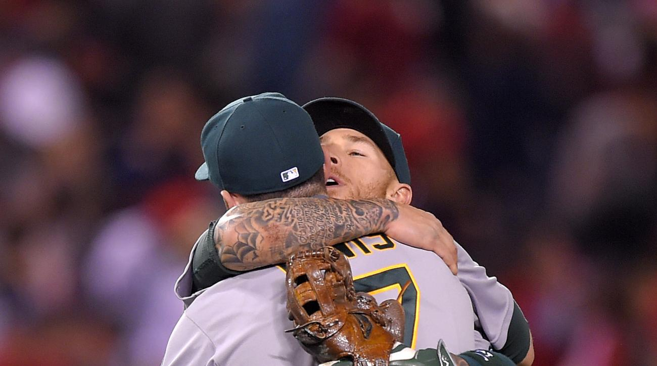 Oakland Athletics' Ike Davis, left, and Brett Lawrie embrace after they defeated the Los Angeles Angels 6-3 in baseball game, Monday, April 20, 2015, in Los Angeles. (AP Photo/Mark J. Terrill)