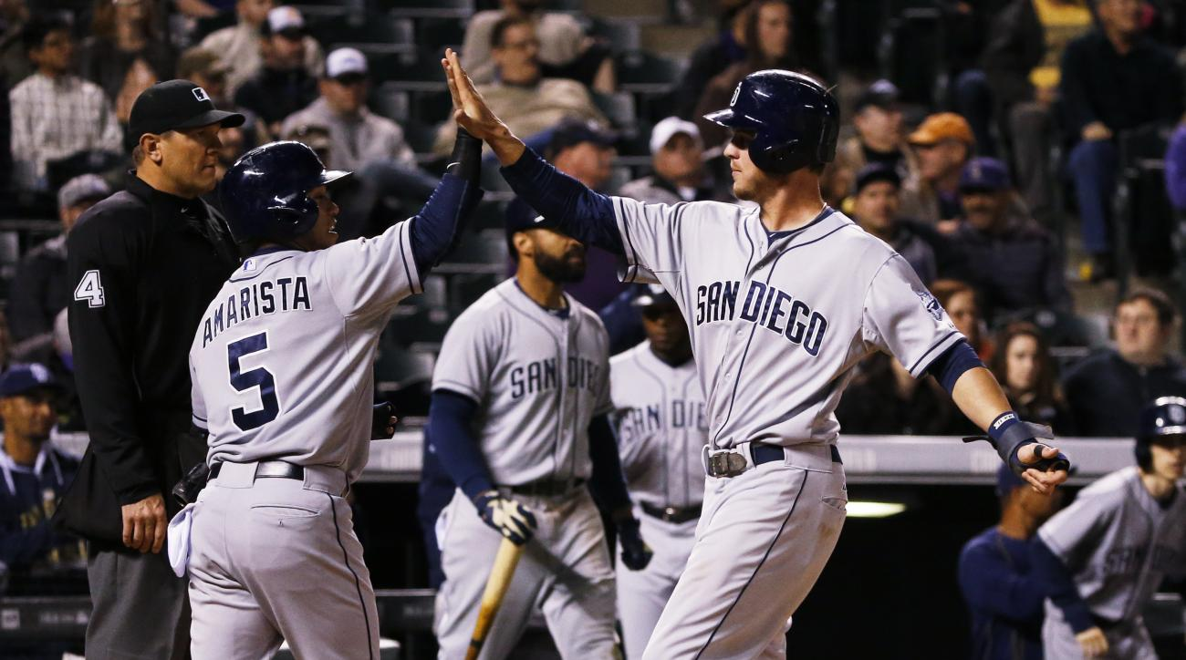 San Diego Padres' Wil Myers, right is congratulated by Alexi Amarista after both scored on a double by Derek Norris against the Colorado Rockies during the eighth inning of a baseball game, Tuesday, April 21, 2015, in Denver. (AP Photo/Jack Dempsey)