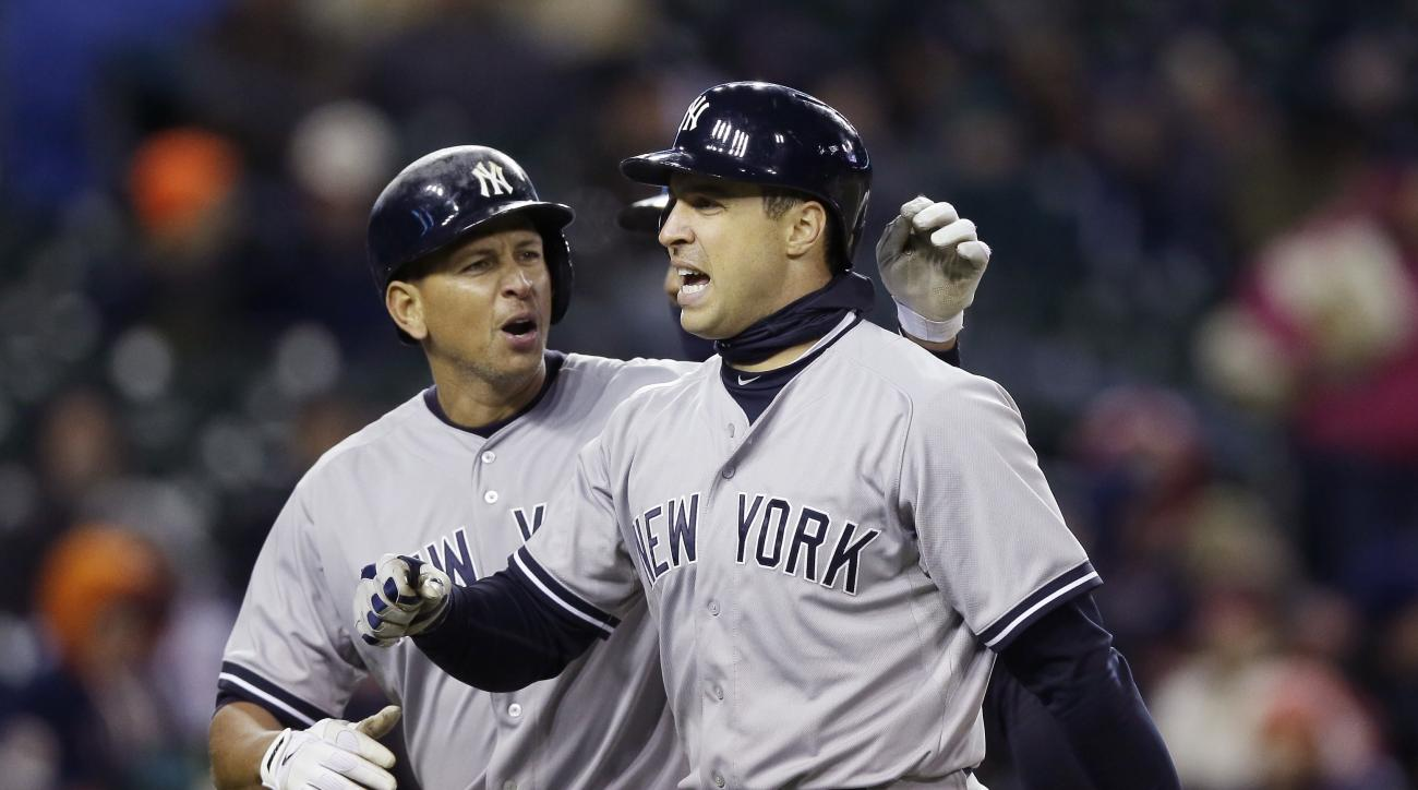New York Yankees' Mark Teixeira, right, is congratulated by Alex Rodriguez after they both scored on Teixeira's three-run home run during the seventh inning of a baseball game against the Detroit Tigers, Wednesday, April 22, 2015, in Detroit. (AP Photo/Ca