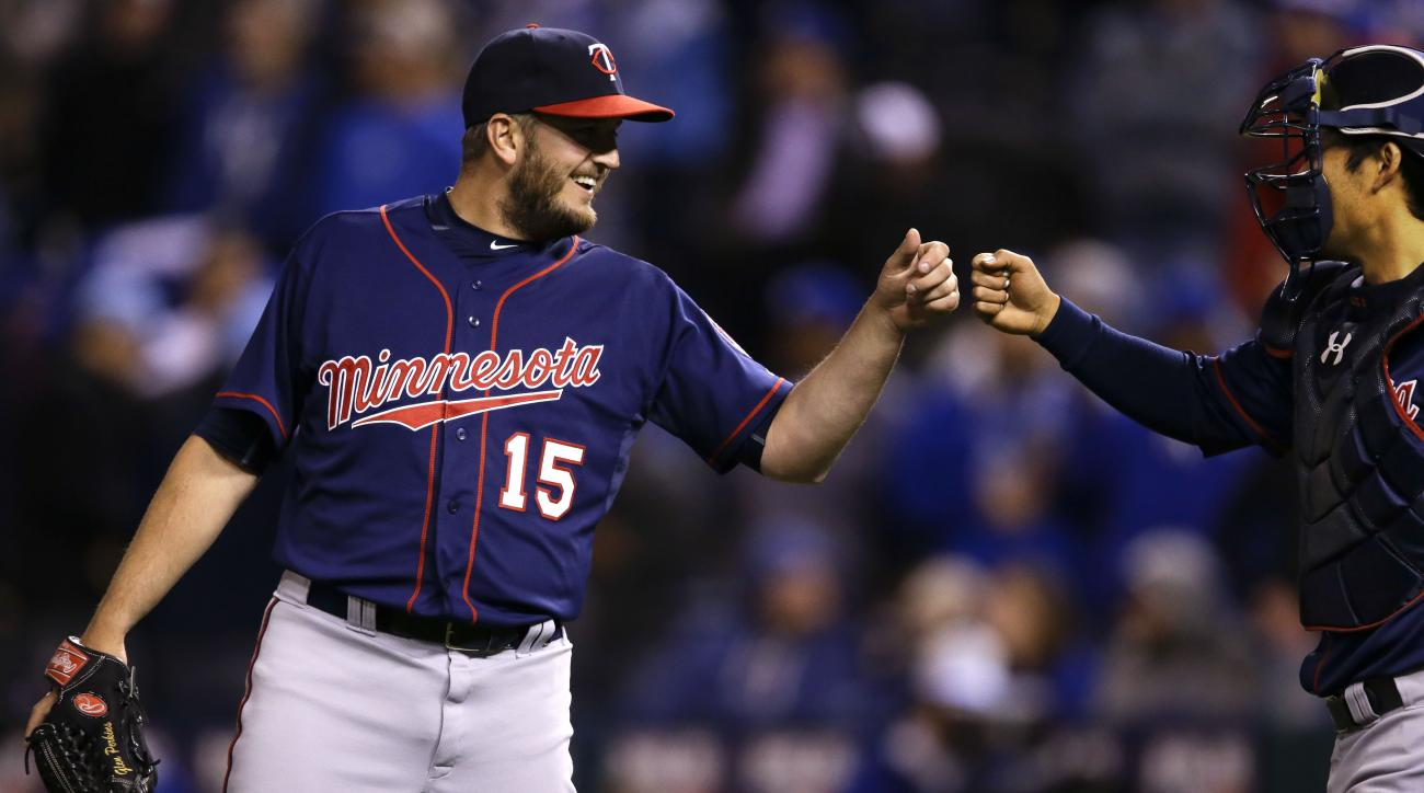 Minnesota Twins relief pitcher Glen Perkins (15) celebrates with catcher Kurt Suzuki, right, following a baseball game against the Kansas City Royals at Kauffman Stadium in Kansas City, Mo., Wednesday, April 22, 2015. The Twins defeated the Royals 3-0. (A