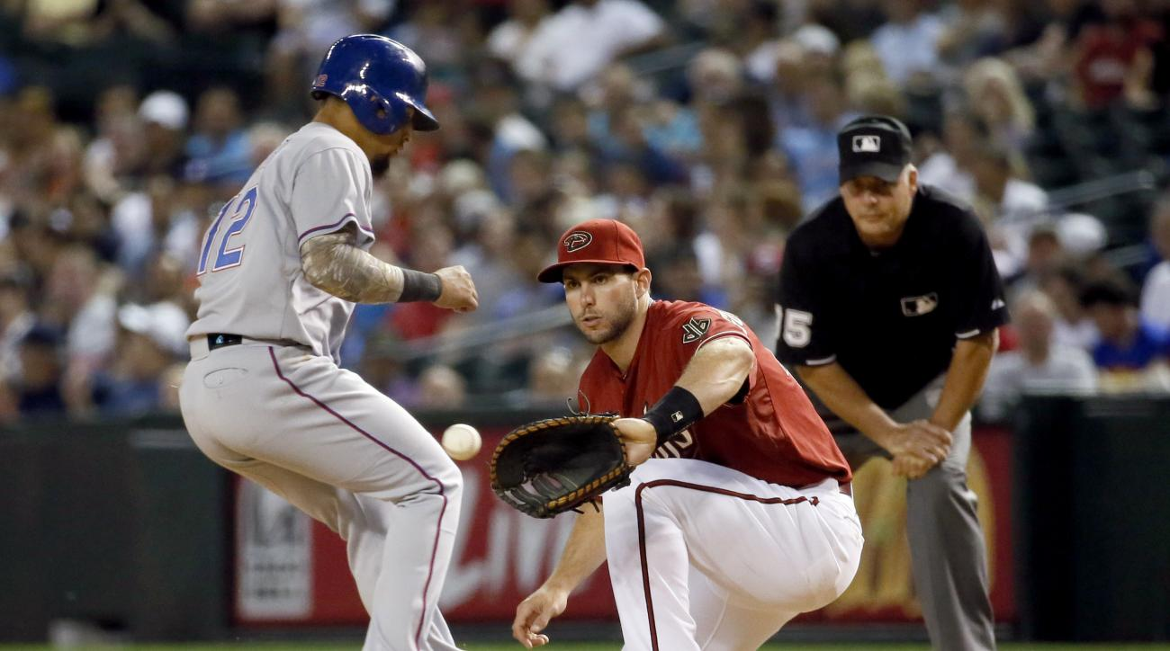 Arizona Diamondbacks first baseman Paul Goldschmidt makes the catch as Texas Rangers' Rougned Odor is safe at first on a pick-off attempt during the seventh inning of a baseball game, Wednesday, April 22, 2015, in Phoenix. (AP Photo/Matt York)