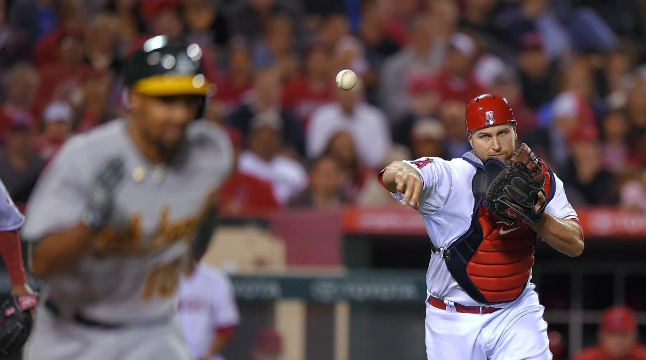 Oakland Athletics' Marcus Semien, left, is thrown out at first by Los Angeles Angels catcher Chris Iannetta during the seventh inning of a baseball game, Wednesday, April 22, 2015, in Anaheim, Calif. (AP Photo/Mark J. Terrill)