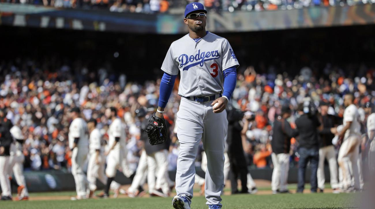 Los Angeles Dodgers' Carl Crawford walks off the field as the San Francisco Giants celebrate a 3-2 win behind him in a baseball game on Thursday, April 23, 2015, in San Francisco. (AP Photo/Marcio Jose Sanchez)