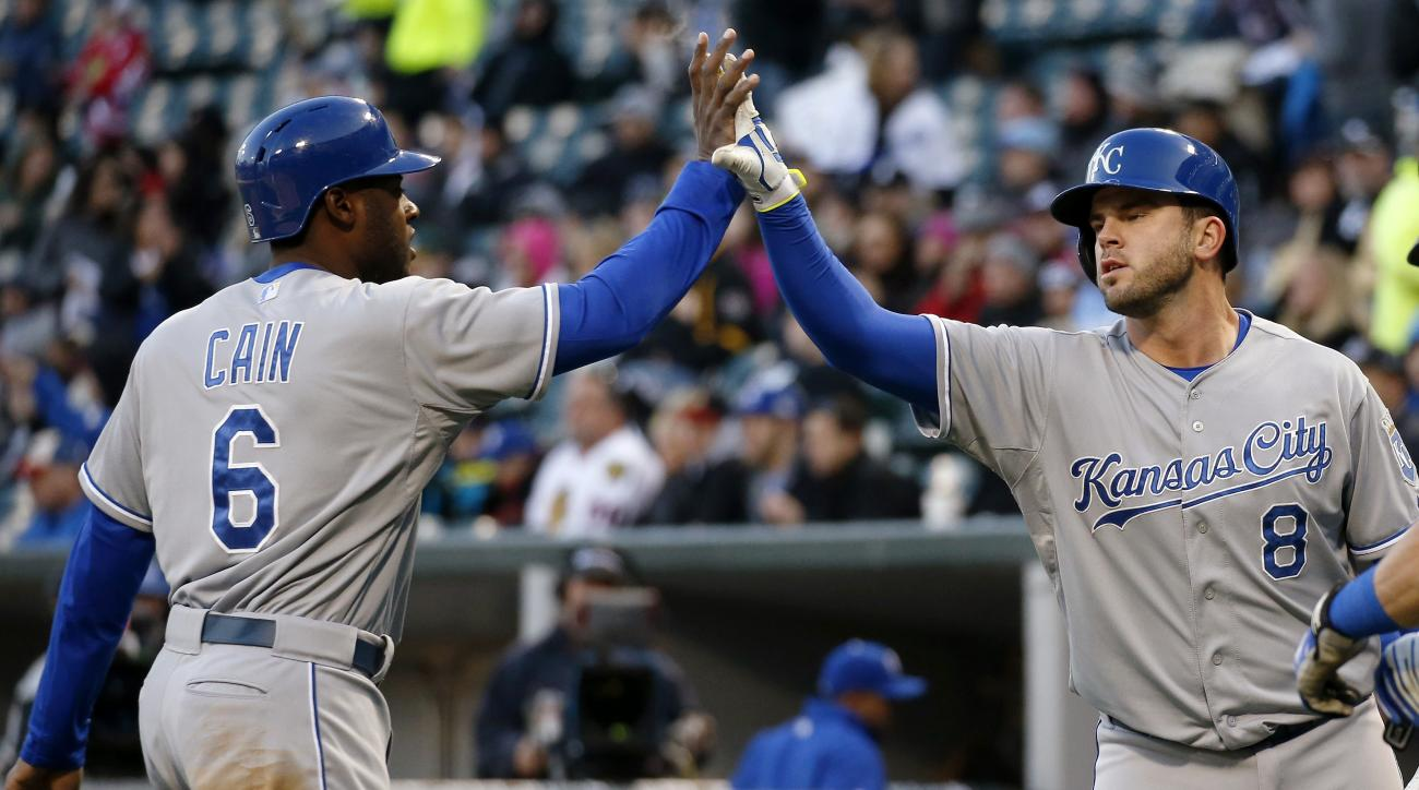 Kansas City Royals' Lorenzo Cain (6) and Mike Moustakas (8) celebrate after scoring on a hit by Kendrys Morales against the Chicago White Sox during the first inning of a baseball game Thursday, April 23, 2015, in Chicago. (AP Photo/Andrew A. Nelles)