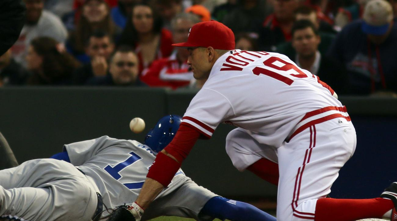 Cincinnati Reds' Joey Votto misses the throw from the pitcher as Chicago Cubs' Kris Bryant dives back to first base during the fifth inning of a baseball game Friday, April 24, 2015, in Cincinnati. (AP Photo/Tom Uhlman)