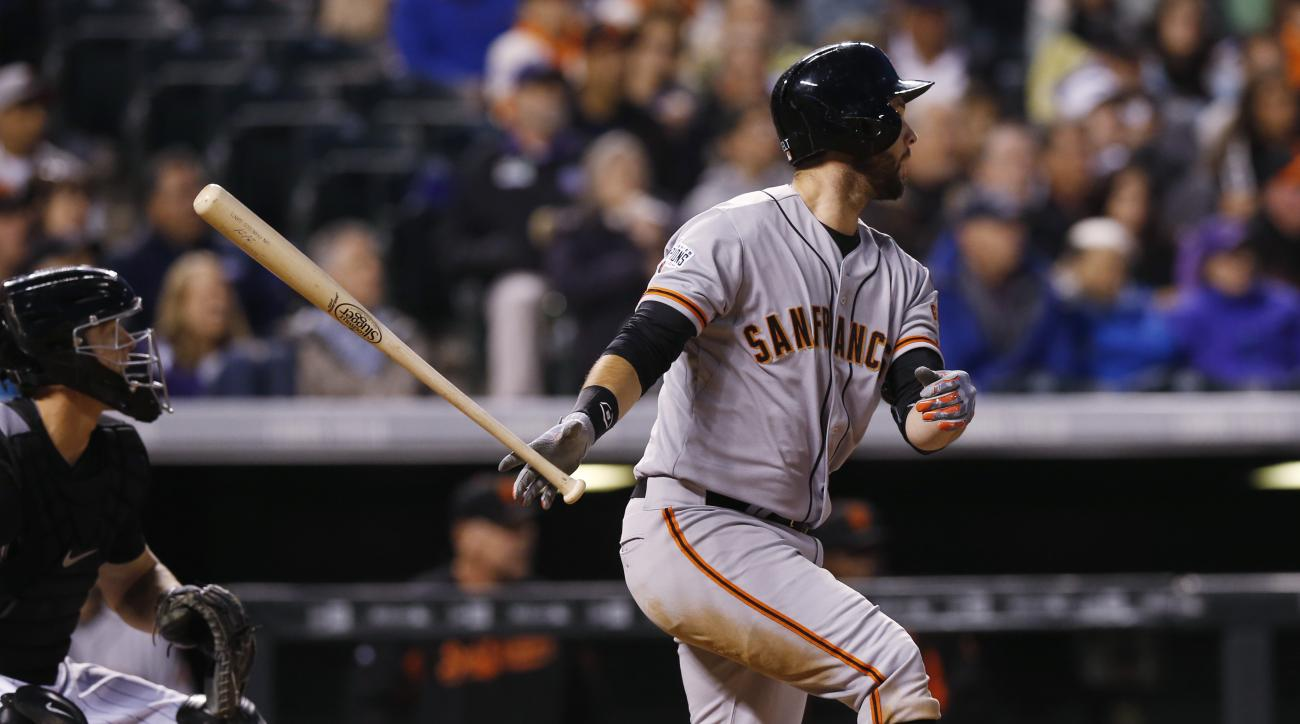 San Francisco Giants' Brandon Belt, right, follows the flight of his RBI-double with Colorado Rockies catcher Nick Hundley in the fifth inning of a baseball game Friday, April 24, 2015, in Denver. (AP Photo/David Zalubowski)
