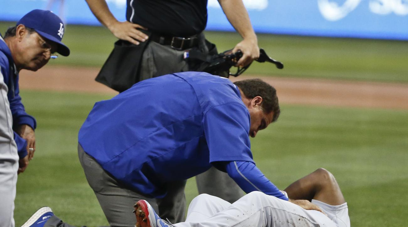 Los Angeles Dodgers' Yasiel Puig is attended to at home plate after being hit in the knee by a pitch from San Diego Padres starting pitcher Andrew Cashner in the first inning of a baseball game Friday, April 24, 2015 in San Diego. (AP Photo/Lenny Ignelzi)