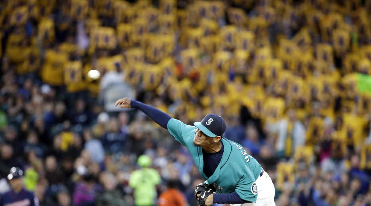 """Seattle Mariners starting pitcher Felix Hernandez throws, with a backdrop of yellow """"K"""" strikeout cards held by fans, during the fifth inning of the Mariners' baseball game against the Minnesota Twins on Friday, April 24, 2015, in Seattle. (AP Photo/Elain"""
