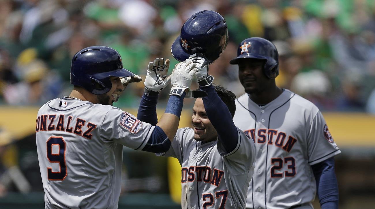 Houston Astros' Jose Altuve (27) celebrates with Marwin Gonzalez (9) and Chris Carter, right, after Altuve hit a three run home run off Oakland Athletics' Kendall Graveman in the second inning of a baseball game Saturday, April 25, 2015, in Oakland, Calif