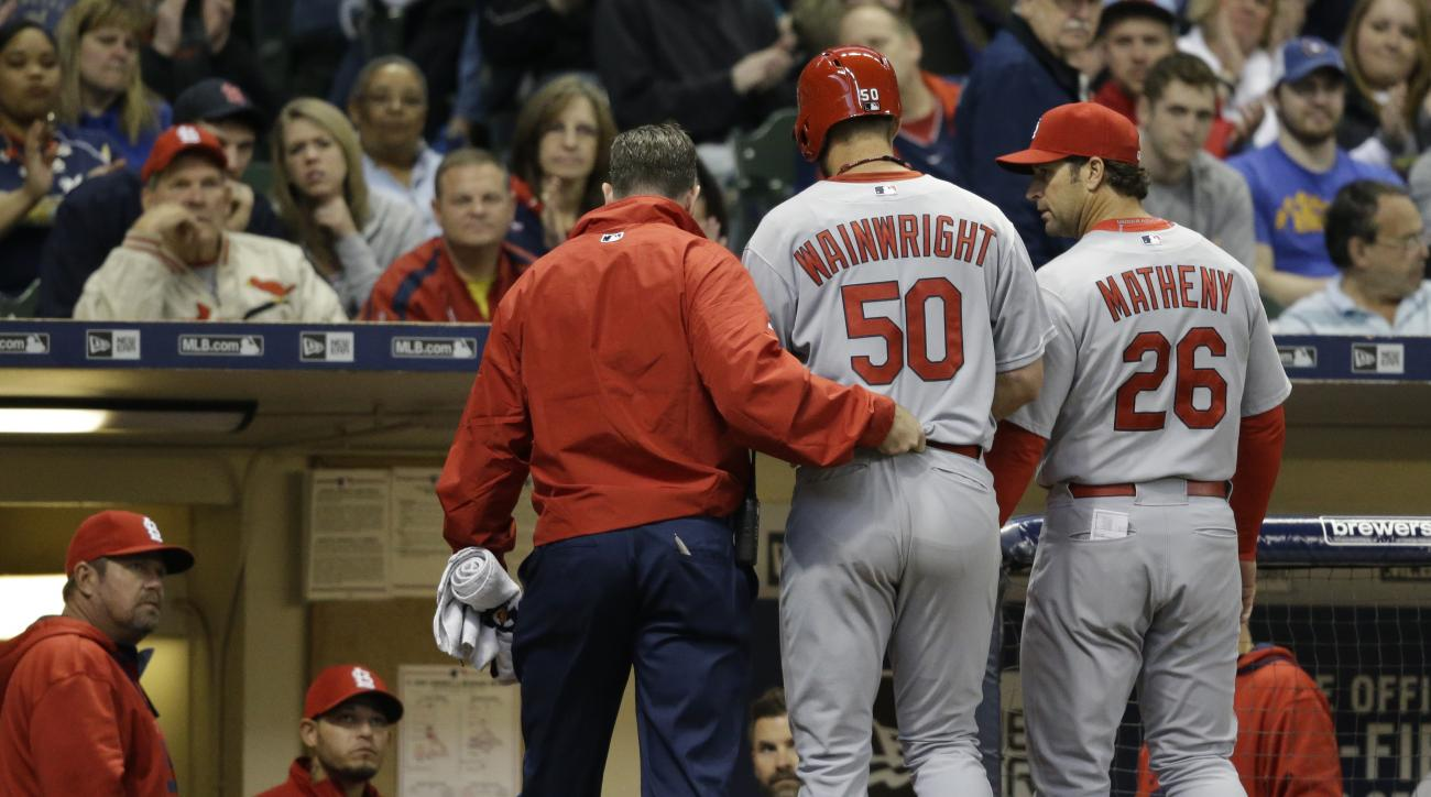 St. Louis Cardinals starting pitcher Adam Wainwright (50) is helped off the field after getting injured while batting during the fourth inning of a baseball game against the Milwaukee Brewers Saturday, April 25, 2015, in Milwaukee.  (AP Photo/Jeffrey Phel