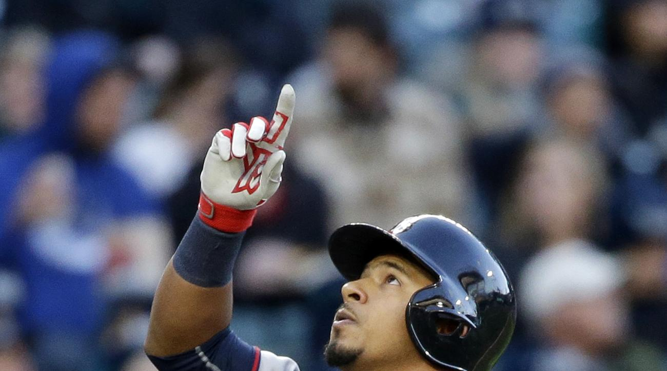 Minnesota Twins' Eduardo Escobar points skyward as he crosses the plate on his home run against the Seattle Mariners during the fourth inning of a baseball game Saturday, April 25, 2015, in Seattle. (AP Photo/Elaine Thompson)