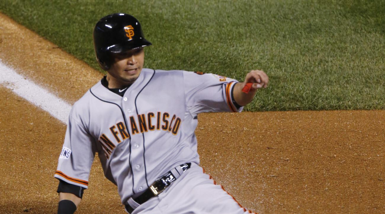San Francisco Giants' Nori Aoki scores the go-ahead run on a bunt by Joe Panik against the Colorado Rockies in the 11th inning of a baseball game Saturday, April 25, 2015, in Denver. The Giants won 5-4 in 11 innings.(AP Photo/David Zalubowski)
