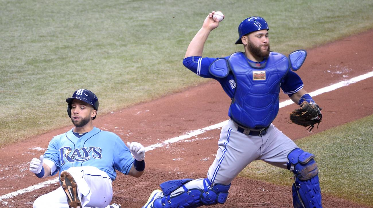 Toronto Blue Jays catcher Russell Martin, right, throws to first base to complete a double play against Tampa Bay Rays' Rene Rivera after getting the force-out on Rays' James Loney, left, at home plate during the sixth inning of a baseball game in St. Pet