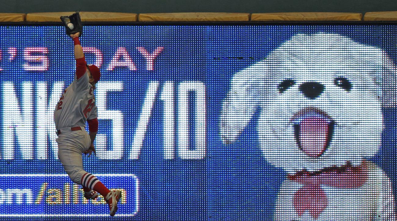 St. Louis Cardinals' Mark Reynolds makes a leaping catch on a ball hit by Milwaukee Brewers' Adam Lind during the seventh inning of a baseball game Sunday, April 26, 2015, in Milwaukee. (AP Photo/Jeffrey Phelps)