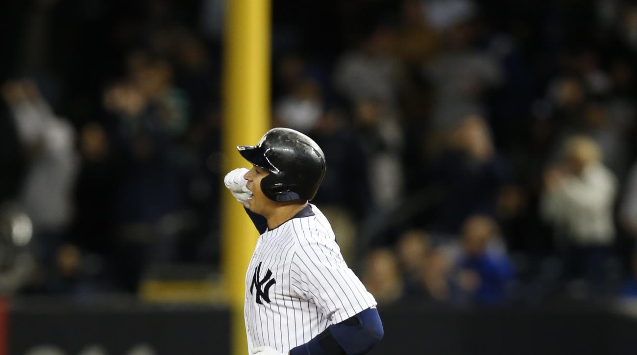 New York Yankees designated hitter Alex Rodriguez celebrates as he runs the bases on his first-inning, solo home run, against the New York Mets at Yankee Stadium in New York, Sunday, April 26, 2015.  (AP Photo/Kathy Willens)