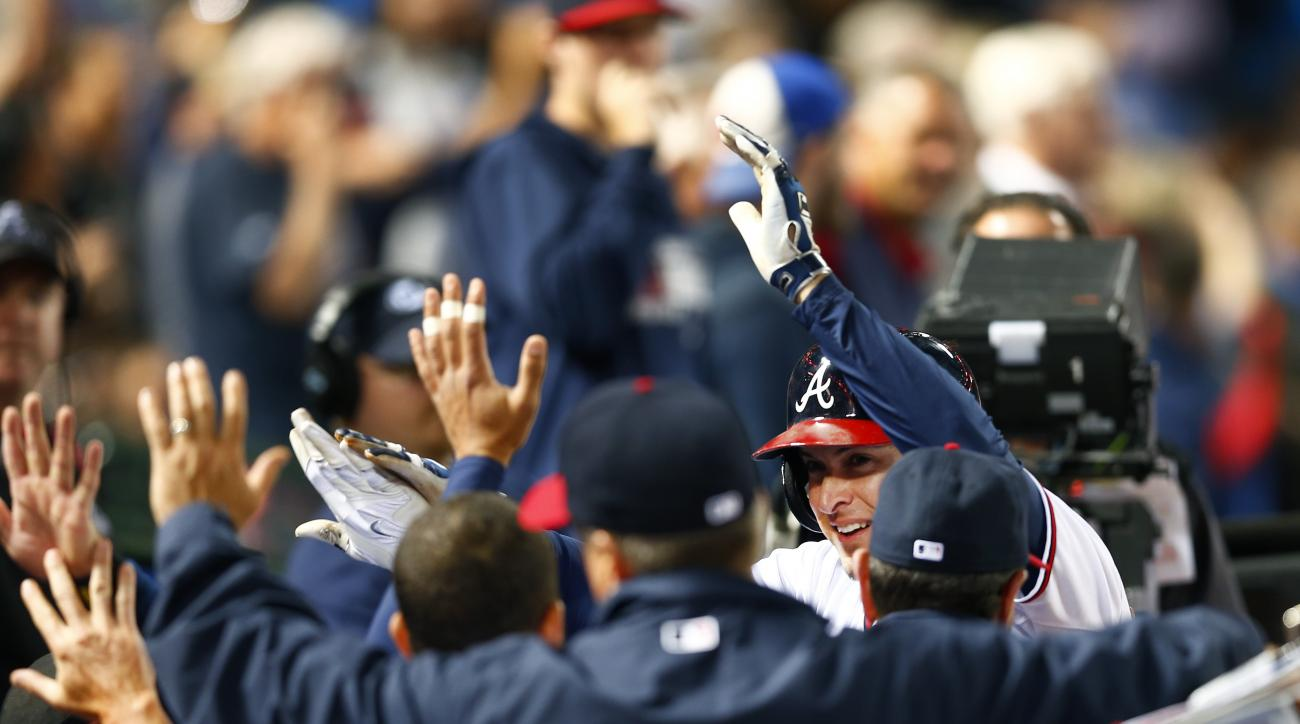 Atlanta Braves left fielder Kelly Johnson, right, is greeted at the dugout by his teammates after hitting a two-run home run in the sixth inning of  a baseball game against the Washington Nationals, Monday, April 27, 2015, in Atlanta. (AP Photo/John Bazem