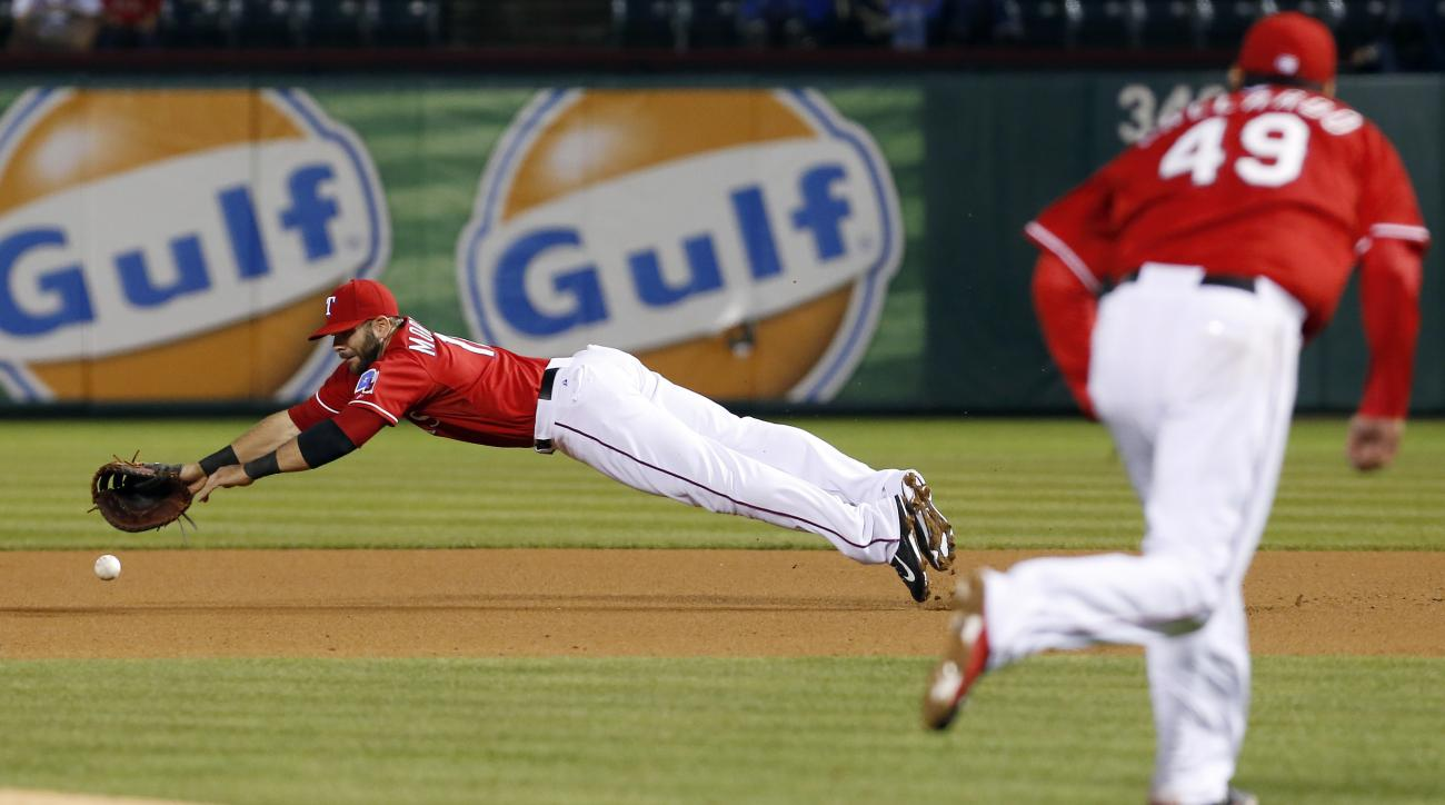 Texas Rangers starting pitcher Yovani Gallardo (49) looks on as first baseman Mitch Moreland dives to field a hit by Seattle Mariners designated hitter Rickie Weeks, not pictured, during the fourth inning of a baseball game, Monday, April 27, 2015, in Arl