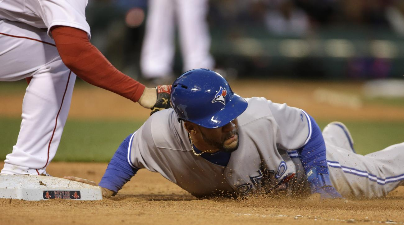 Toronto Blue Jays' Devon Travis, right, jumps back to first base to survive a pick-off attempt as Boston Red Sox's Daniel Nava, left, tries to tag him in the fourth inning of a baseball game Tuesday, April 28, 2015, in Boston. (AP Photo/Steven Senne)