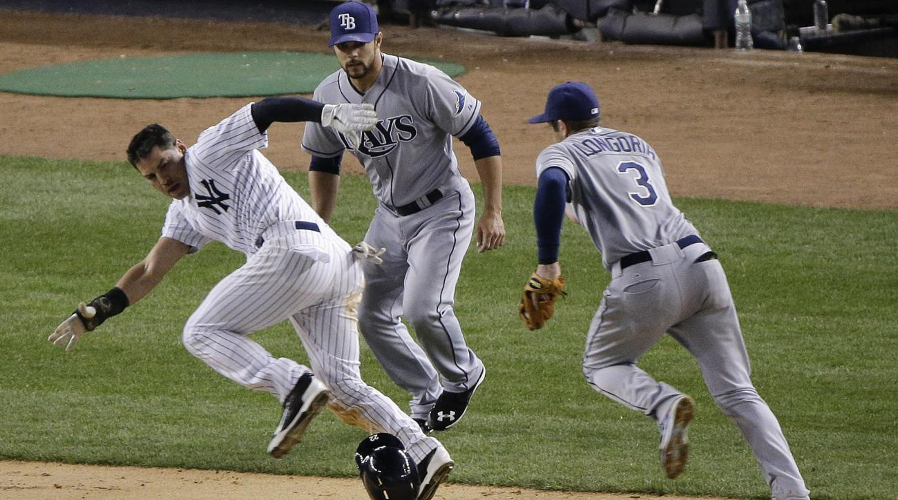 New York Yankees center fielder Jacoby Ellsbury, left, is caught in a rundown as Tampa Bay Rays third baseman Evan Longoria (3) chases him down between third and home as pitcher Xavier Cedeno looks on in the seventh inning of a baseball game, Tuesday, Apr
