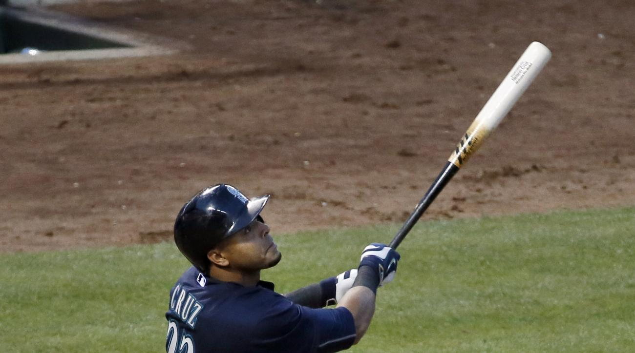 Seattle Mariners' Nelson Cruz follows through on a triple to right off a pitch from Texas Rangers starting pitcher Ross Detwiler in the fourth inning of a baseball game Tuesday, April 28, 2015, in Arlington, Texas. (AP Photo/Tony Gutierrez)