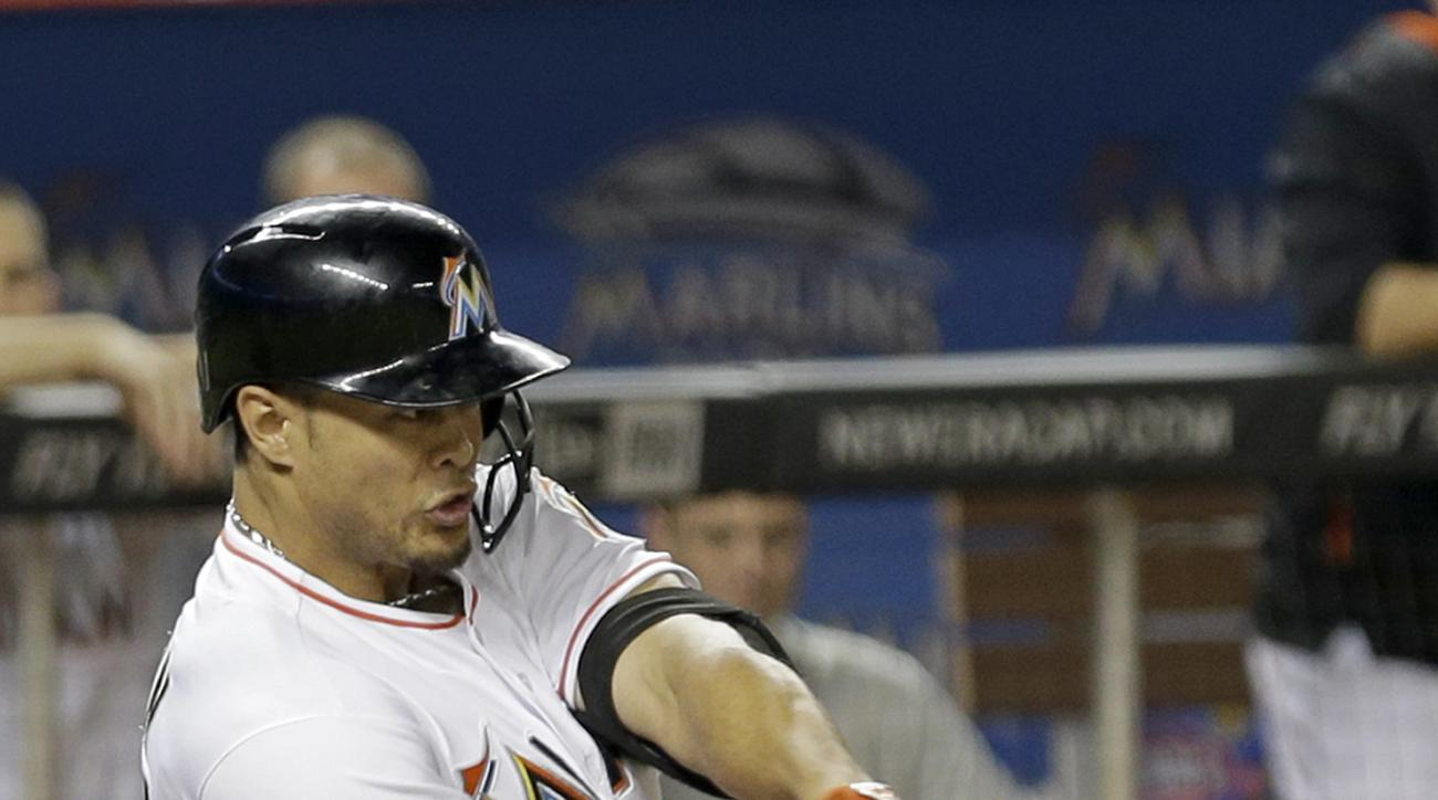 Miami Marlins' Giancarlo Stanton (27) hits a single against the New York Mets driving in teammate Dee Gordon in the sixth inning of a baseball game, Tuesday, April 28, 2015, in Miami. The Marlins won 4-3. (AP Photo/Alan Diaz)
