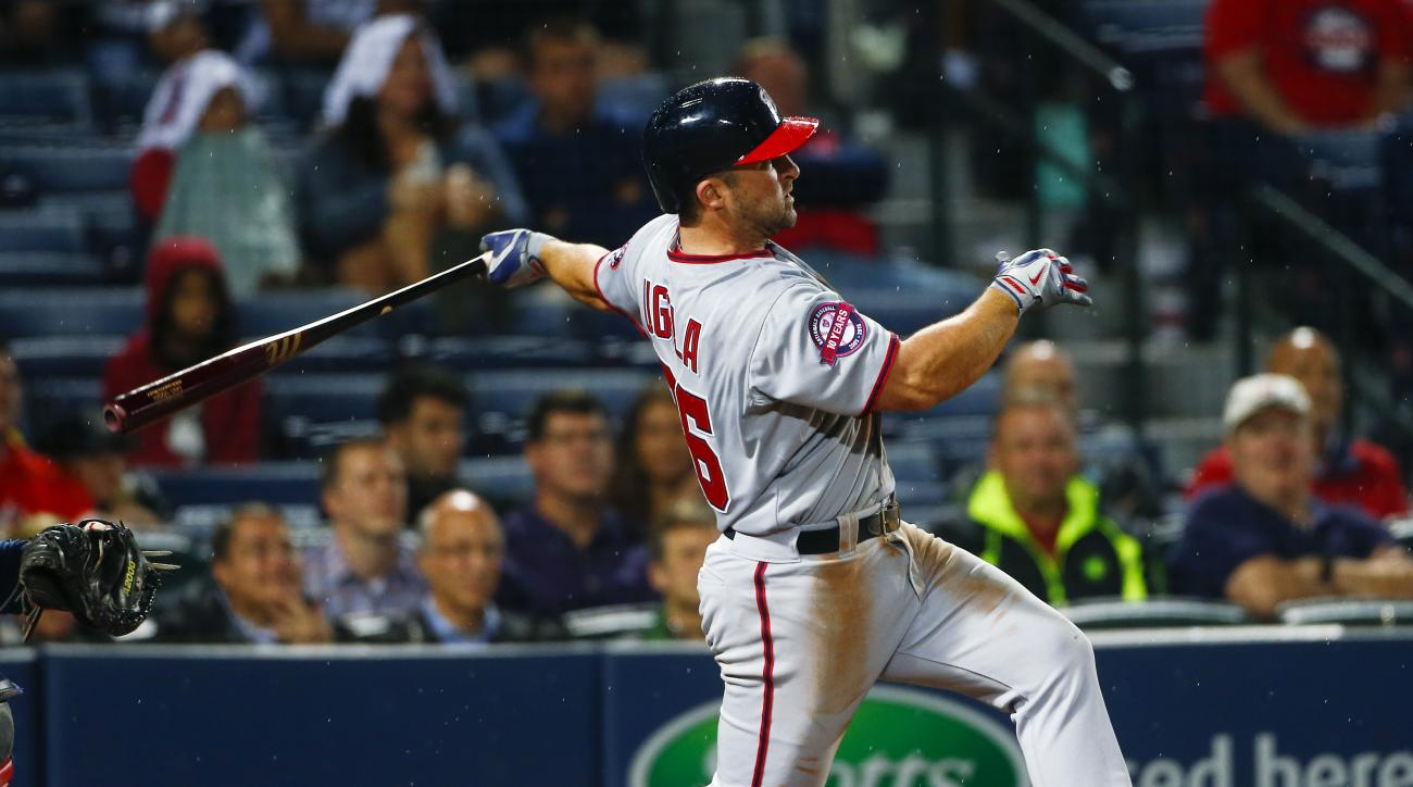 Washington Nationals' Dan Uggla (26) follows through on a three-run home run in the ninth inning of a baseball game against the Atlanta Braves Tuesday, April 28, 2015, in Atlanta. Washington won 13-12. (AP Photo/John Bazemore)