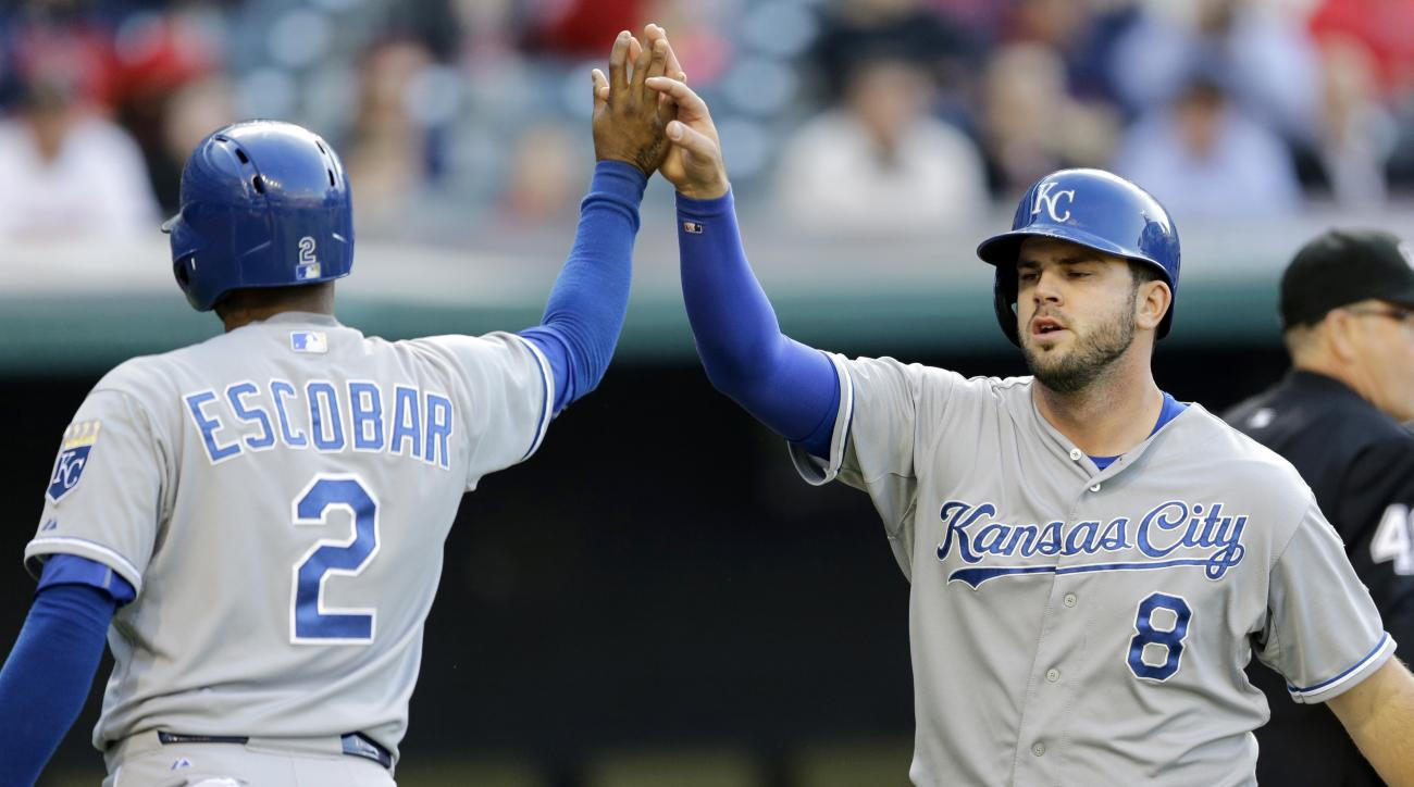 Kansas City Royals' Alcides Escobar (2) and Mike Moustakas (8) celebrate after both score on a two-RBI single hit by Kendrys Morales in the first inning of a baseball game, Wednesday, April 29, 2015, in Cleveland. (AP Photo/Tony Dejak)