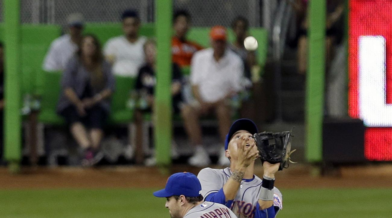 New York Mets shortstop Wilmer Flores (4) prepares to catch a pop-up in shallow left field by Miami Marlins' Adeiny Hechavarria (3) as second baseman Daniel Murphy (28) avoids a collision in the fourth inning of a baseball game, Wednesday, April 29, 2015,