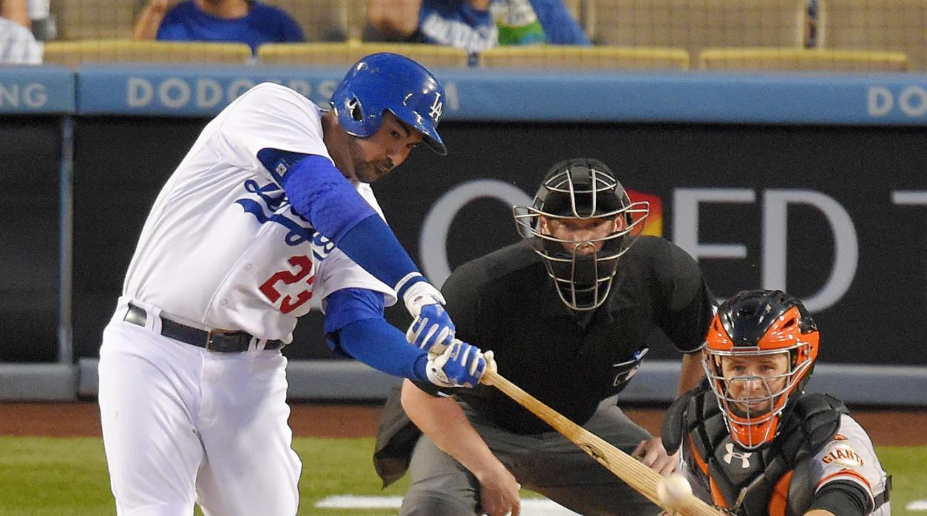 Los Angeles Dodgers' Adrian Gonzalez, left, hits a solo home run as San Francisco Giants catcher Buster Posey, right, catches and home plate umpire Sean Barber watches during the first inning of a baseball game, Wednesday, April 29, 2015, in Los Angeles.