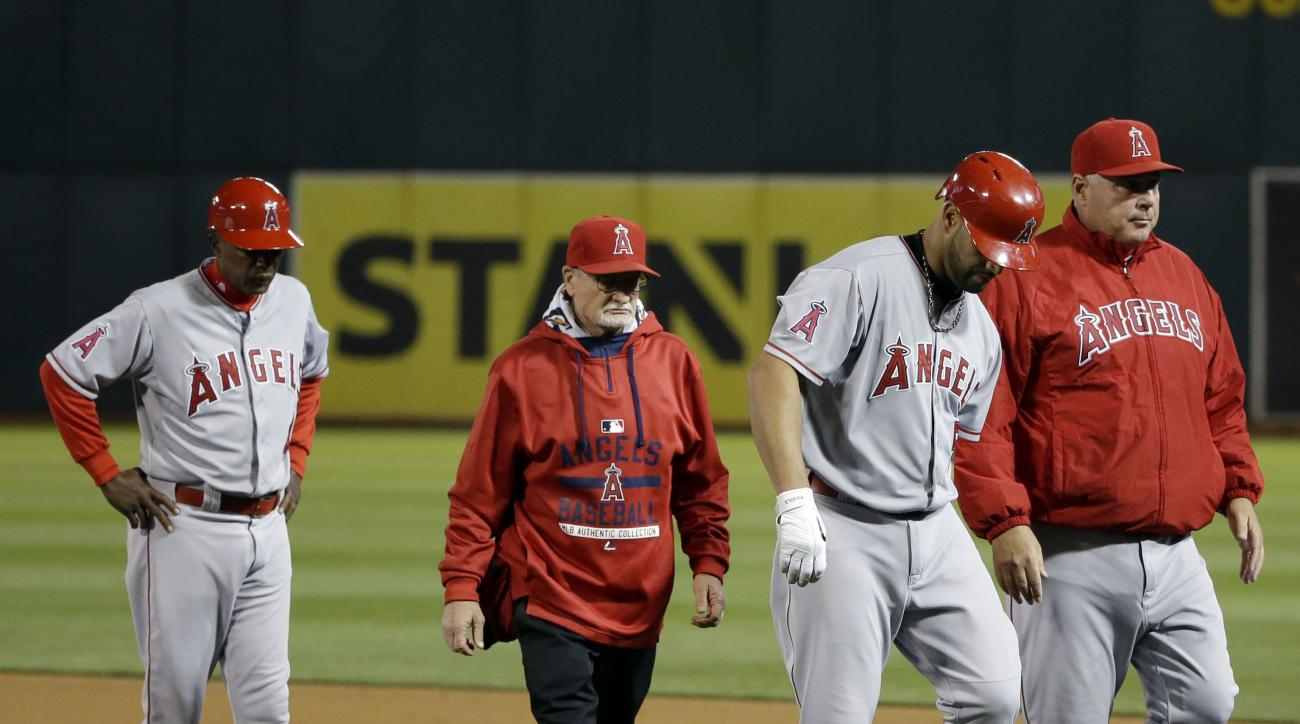 Los Angeles Angels' Albert Pujols, second from right, leaves the game with an injury alongside manager Mike Scioscia, right, during the sixth inning of a baseball game against the Oakland Athletics Wednesday, April 29, 2015, in Oakland, Calif. (AP Photo/M