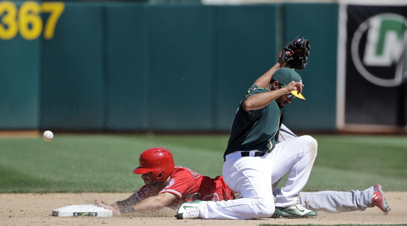 Los Angeles Angels' Taylor Featherston, left, steals second base past Oakland Athletics shortstop Marcus Semien during the eighth inning of a baseball game Thursday, April 30, 2015, in Oakland, Calif. (AP Photo/Marcio Jose Sanchez)