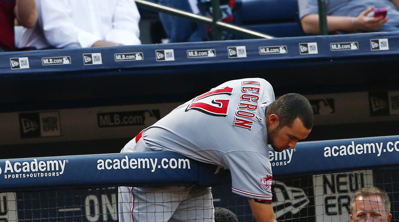 Cincinnati Reds' Kris Negron (17) reaches over the dugout railing for a foul ball during a baseball game against the Atlanta Braves Thursday, April 30, 2015, in Atlanta. (AP Photo/John Bazemore)
