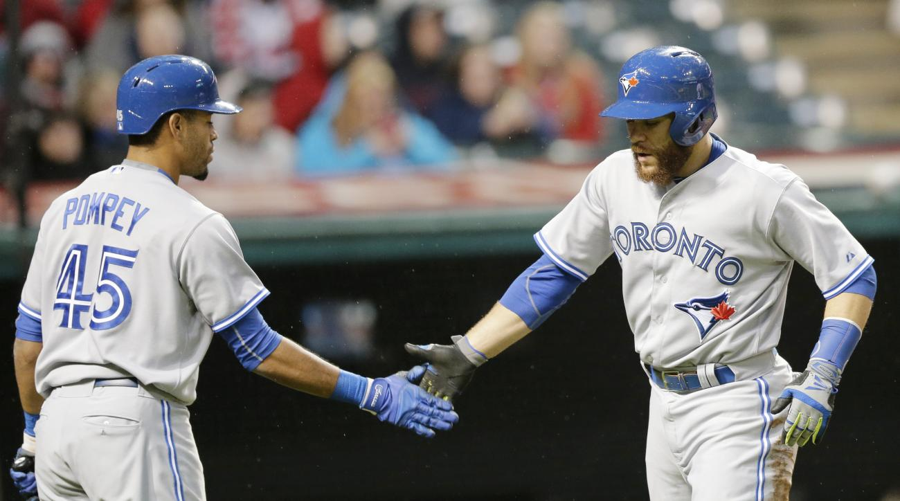 Toronto Blue Jays' Russell Martin, right, is congratulated by Dalton Pompey after scoring on a two-RBI double by Kevin Pillar in the fifth inning of a baseball game against the Cleveland Indians, Thursday, April 30, 2015, in Cleveland. Danny Valencia also