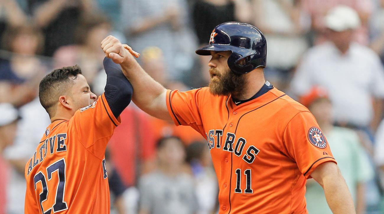 Houston Astros designated hitter Evan Gattis (11) receives a high-five from Jose Altuve, left, after hitting a home run in the first inning against the Seattle Mariners in a baseball game Friday, May 1, 2015 in Houston. (AP Photo/Bob Levey)