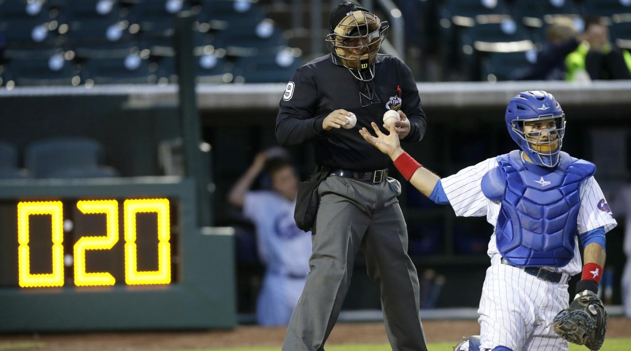 In front of a pace of play clock, home plate umpire Chris Gonzalez gives Iowa Cubs catcher Rafael Lopez a new baseball during a Triple-A baseball game between the Oklahoma City Dodgers and the Iowa Cubs, Friday, May 1, 2015, in Des Moines, Iowa. Slow play