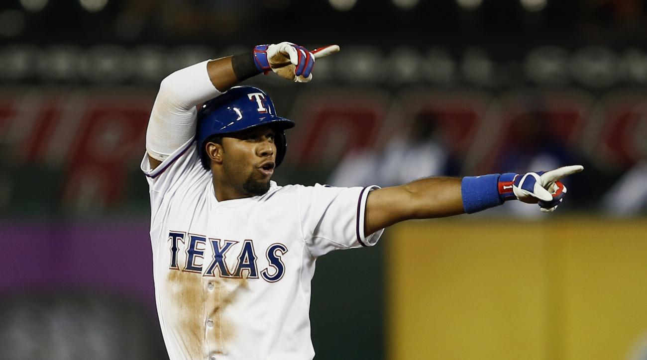 Texas Rangers' Elvis Andrus points to his team dugout after his double against the Oakland Athletics during the fifth inning of a baseball game, Friday, May 1, 2015, in Arlington, Texas, (AP Photo/Jim Cowsert)