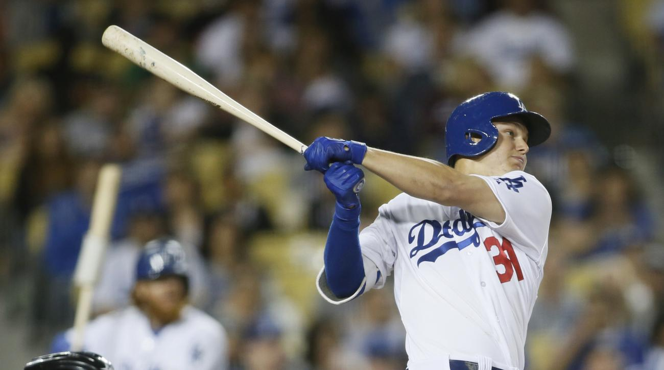 Los Angeles Dodgers' Joc Pederson hits a solo home run in front of Arizona Diamondbacks catcher Jordan Pacheco, left, during the seventh inning of a baseball game, Saturday, May 2, 2015, in Los Angeles. (AP Photo/Danny Moloshok)