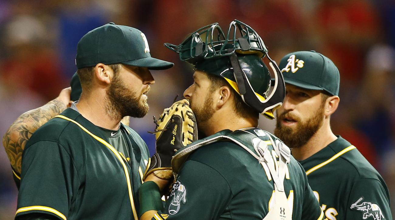 Oakland Athletics catcher Stephen Vogt, center, talks to pitcher Ryan Cook, left, as first baseman Ike Davis listens in the tenth inning of a baseball game against the Texas Rangers Saturday, May 2, 2015, in Arlington, Texas. (AP Photo/Mike Stone)