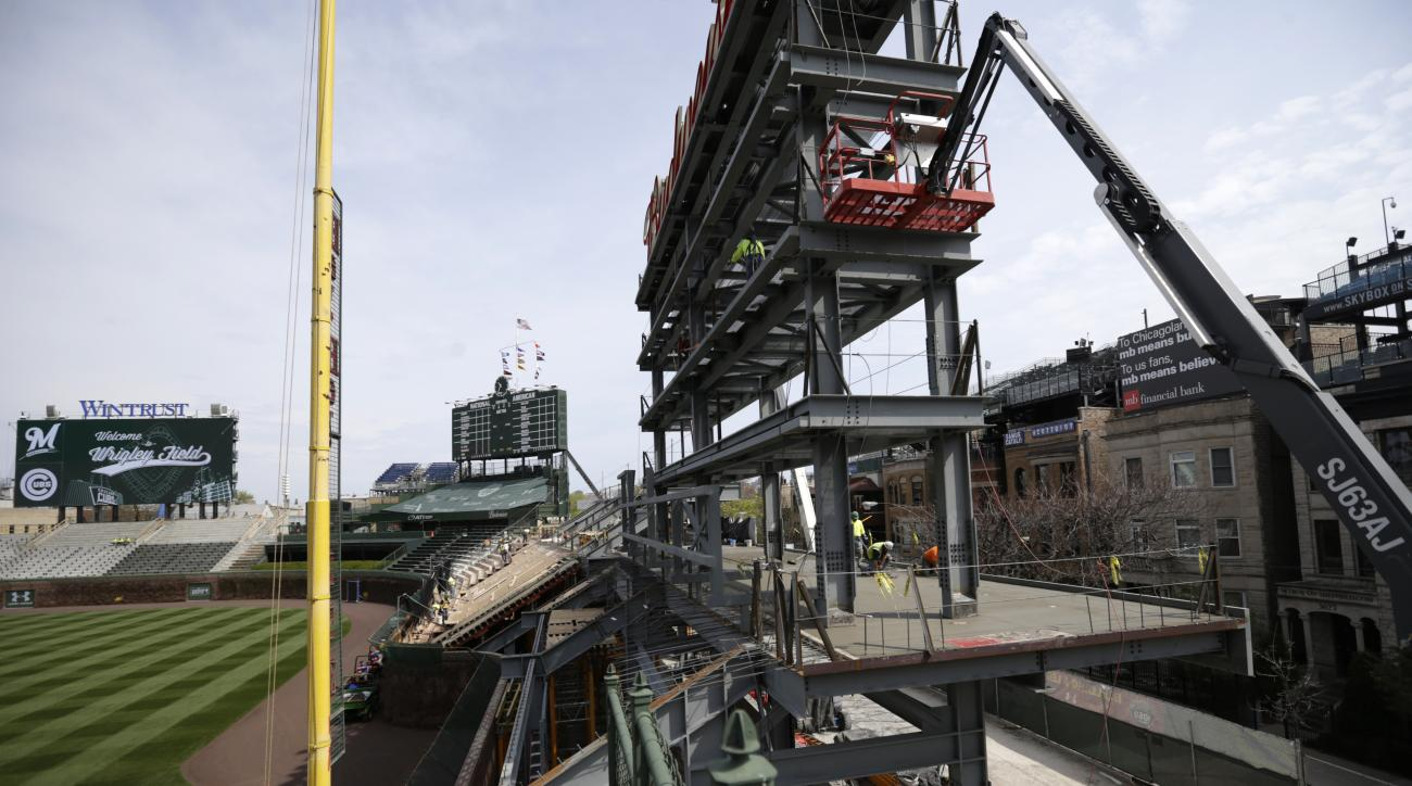 Construction workers attend the new scoreboard in right field at Wrigley Field before a baseball game between the Chicago Cubs and the Milwaukee Brewers in Chicago on Sunday, May 3, 2015. (AP Photo/Jeff Haynes)