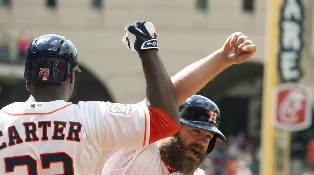 Houston Astros designated hitter Evan Gattis (11) celebrates his solo home run against the Seattle Mariners with teammate Chris Carter (23) in the eighth inning of a baseball game on Sunday, May 3, 2015,  in Houston, Texas. The home run proved to be the g