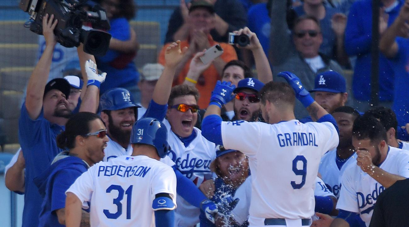 Los Angeles Dodgers' Yasmani Grandal (9) jumps onto home plate as the rest of his team celebrates after he hit a walkoff home run in the 13th inning of a baseball game against the Arizona Diamondbacks, Sunday, May 3, 2015, in Los Angeles. (AP Photo/Mark J