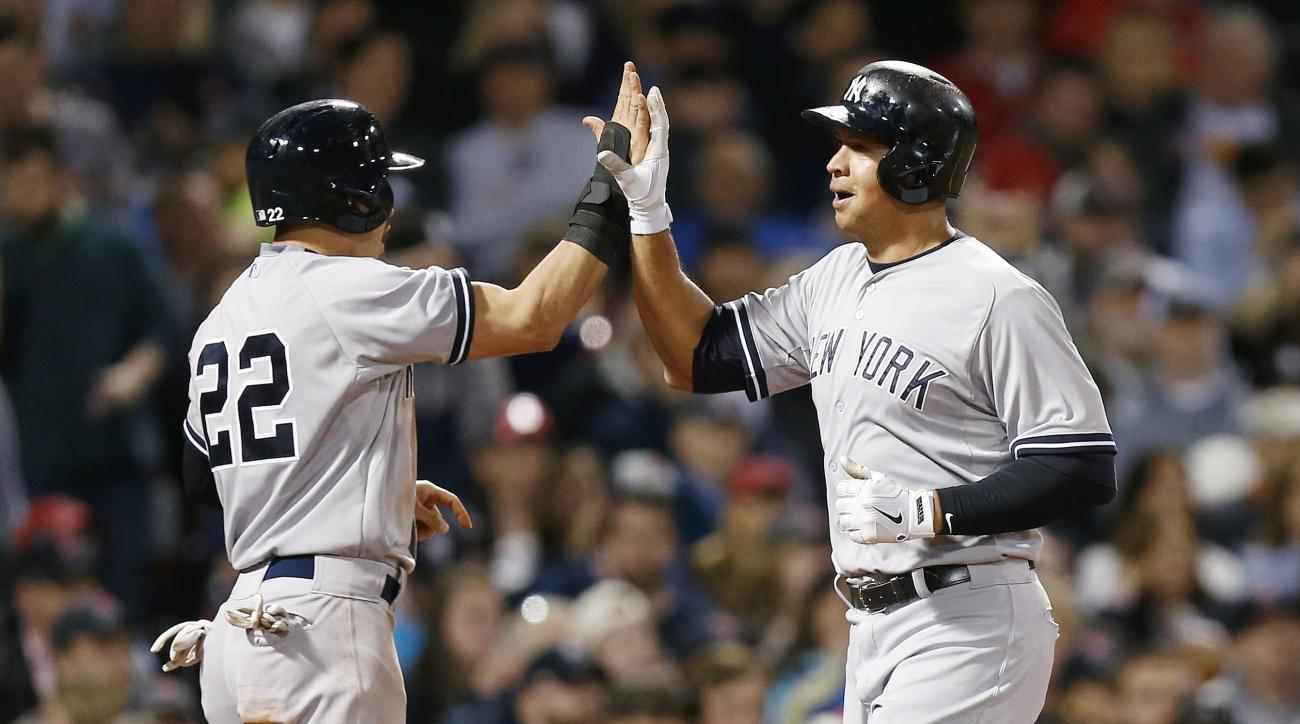 New York Yankees' Alex Rodriguez, right, celebrates after scoring with Jacoby Ellsbury (22) on a two-run double by Brian McCann during the third inning of a baseball game against the Boston Red Sox in Boston, Sunday, May 3, 2015. (AP Photo/Michael Dwyer)