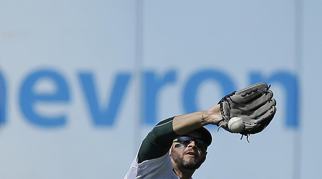 Oakland Athletics' Cody Ross drops a ball hit by Houston Astros' Colby Rasmus in the seventh inning of a baseball game Saturday, April 25, 2015, in Oakland, Calif. (AP Photo/Ben Margot)